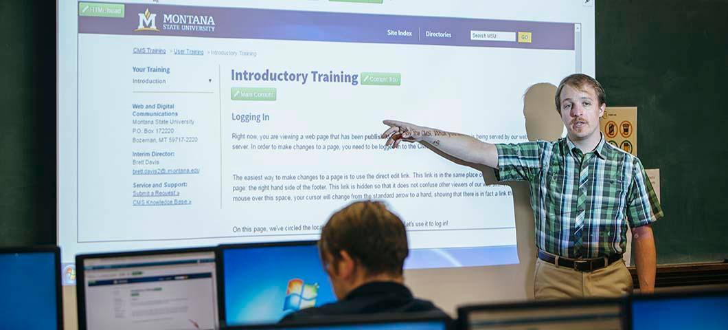 "A CMS training instructor points to the words ""Introductory Training"" displayed on the projector screen while a man sitting in front of a computer observes."